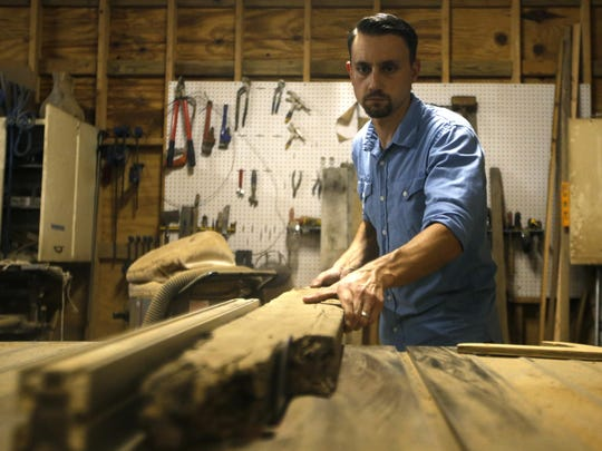 Barry Miller saws reclaimed wood in his Tallahassee woodworking shop on Sept. 9. Miller creates handcrafted designs from his shop, Rose Boulevard custom wood furniture.
