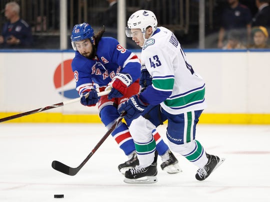 New York Rangers center Mika Zibanejad (93) of Sweden defends as Vancouver Canucks defenseman Quinn Hughes (43) in the second period of a NHL hockey game, Sunday, Oct. 20, 2019, in New York. (AP Photo/Kathy Willens)