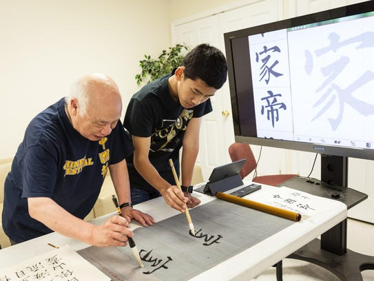 George C. Hsiao, left, and a student work on shu fa,