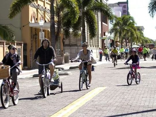 Bicyclists ride the streets of downtown Fort Myers.