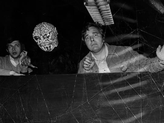 Two of WSAI's zaniest characters, deejays Casey Piotrowski (left) and Buddy Baron, peer out over one of the sets at the radio station's haunted house.