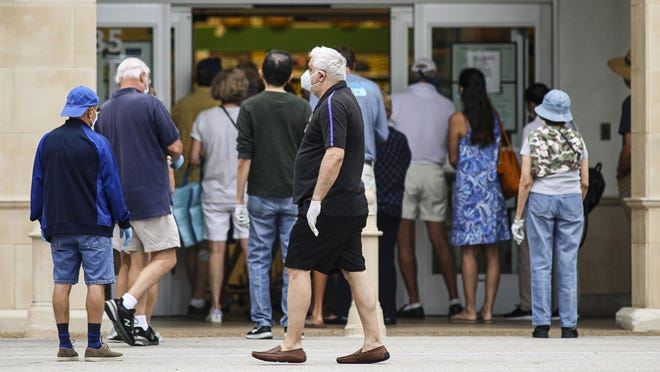 A crowd of people, most of whom were wearing protective masks and gloves, enter Publix in Palm Beach after the doors opened just before 8 am, Sunday, April 5, 2020.  [Damon Higgins/palmbeachdailynews.com]\r\r\r
