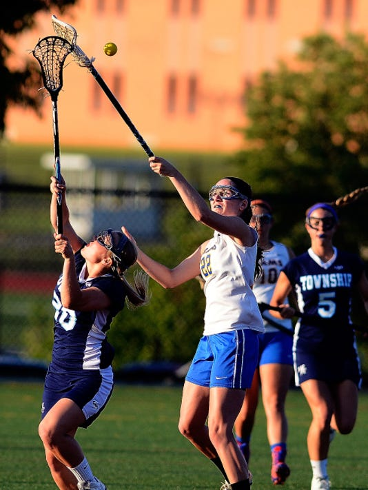 Hannah Wertz of Manheim Township, left, and Morgan Day of Kennard-Dale battle for the ball during a District 3 semifinal lacrosse game at Hershey High School on Tuesday. Manheim Township won the match, 16-9.