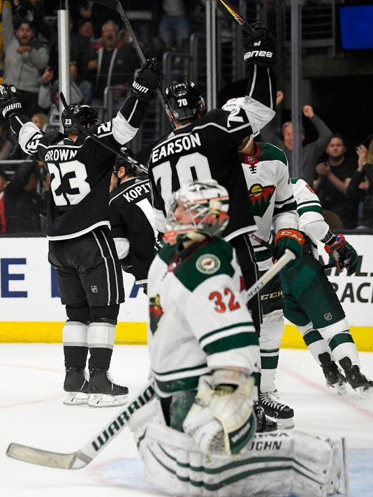 Los Angeles Kings right wing Dustin Brown, left, celebrates his third goal of the game with left wing Tanner Pearson, center, as Minnesota Wild goaltender Alex Stalock kneels on the ice during the second period of an NHL hockey game Thursday, April 5, 2018, in Los Angeles. (AP Photo/Mark J. Terrill)