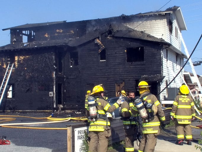 Firefighters are shown behind 2119 Long Beach Boulevard in Ship Botton Monday, July 7, 2014, after working to extinguish a fire there.   SHIP BOTTOM, NJ    SHIPBOTTOMFIRE0707A  With Video   STAFF PHOTO BY THOMAS P. COSTELLO / ASBURY PARK PRESS