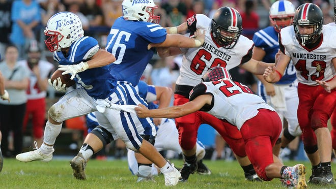 Tuslaw's Aaron Swogger (76) helps to open up a hole for Brier Marthey to run through during a game against Manchester on Friday, Sept. 14, 2018