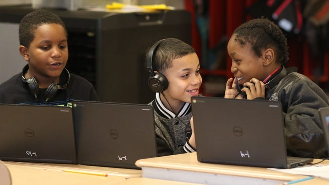 Third graders Drevon Nauden, Jose Rivera and Julius Greer play a computer game together during free time at School 8.