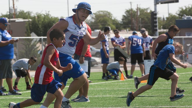 Jesus Villegas, races David Valles,7, a camper at the Bulldawg Football Camp during sprinting drills on Thursday at the Las Cruces High School.