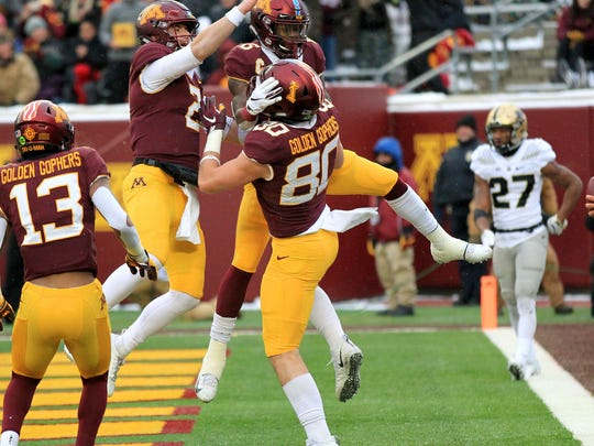 Minnesota tight end Jake Paulson (80) celebrates his touchdown catch with teammates Tanner Morgan (2), Tyler Johnson (6) and Rashod Bateman (13) on Nov. 10, 2018, in Minneapolis.