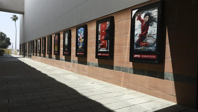 Posters for upcoming movies are displayed in an empty corridor at the currently closed AMC Burbank Town Center 8 movie theaters complex in Burbank, Calif. After several false starts, the film industry is hoping to bring new releases back into movie theaters in late August. Theater owners say if they don't get new films soon, they may not make it to 2021.