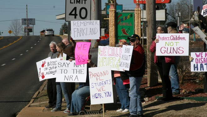 """Members of the Unitarian Universalist Fellowship of Mountain Home and the Buffalo River chapter of Indivisible convened Wednesday morning at what they have dubbed """"Protest Corner,"""" across from the local offices of US Congressman Rick Crawford and US Senator John Boozman. The crowd of roughly 20 area residents held signs and waved at passing drivers in a show of solidarity with nationwide school walkouts on the one-month anniversary of the Parkland, Fla. school shooting."""