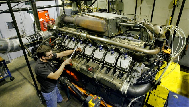 A technician works on a large engine at what then was known as Waukesha Engine on Oct. 18, 2005.