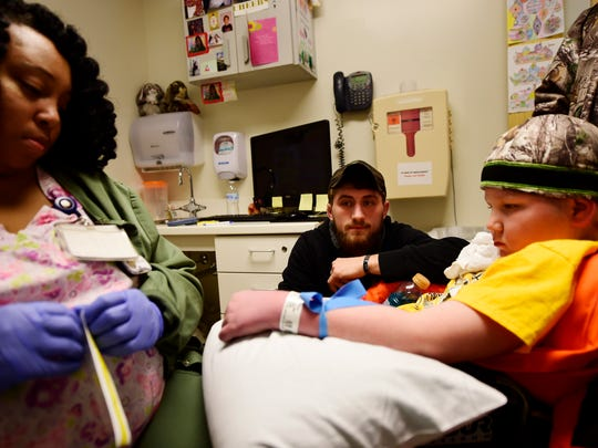 """Arian Kohler, center, watches as clinical technician Lakisha Bey starts an IV in the arm of Ayden Zeigler-Kohler, 10, at John Hopkins Hospital on March 16. Arian, a former Marine, had just moved from North Carolina to be with his brother at the end of his life. """"You're not going in to the military,"""" Kohler told his little brother. """"You're going to to go college."""""""