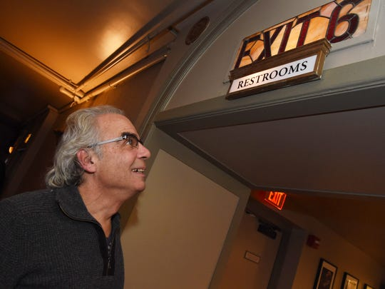 Chris Silva, executive director of the Bardavon 1869 Opera House, looks up at a vintage sign for the bathroom during the unveiling of renovations to the Ulster Performing Arts Center. The bathrooms were the most visible parts of the renovations.