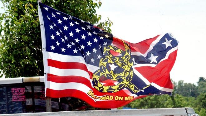 "A flag bringing together images of the current U.S. flag, the Confederate battle flag and the ""Don't Tread on Me"" symbol popular during the American Revolution, waves from the back of back of a pickup truck in Wooster earlier this month."