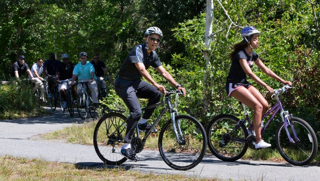 Followed by Secret Service agents, President Obama bike rides with daughter Malia Obama.