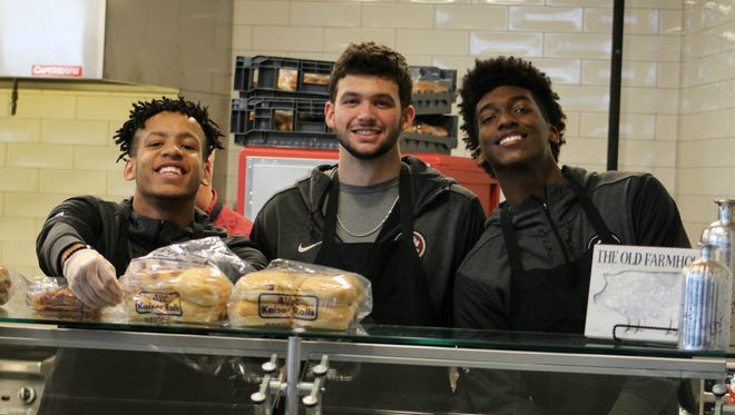 (From left) FSU men's basketball players CJ Walker, Wyatt Wilkes and Terrance Mann served food at the Champions Club to students in need of a meal after Hurricane Irma.