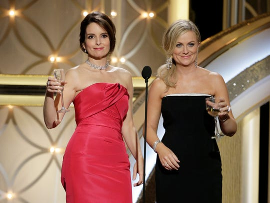 This image released by NBC shows hosts Tina Fey, left, and Amy Poehler during the 71st annual Golden Globe Awards at the Beverly Hilton Hotel on Sunday, Jan. 12, 2014, in Beverly Hills, Calif. (AP Photo/NBC, Paul Drinkwater) ORG XMIT: NYET817