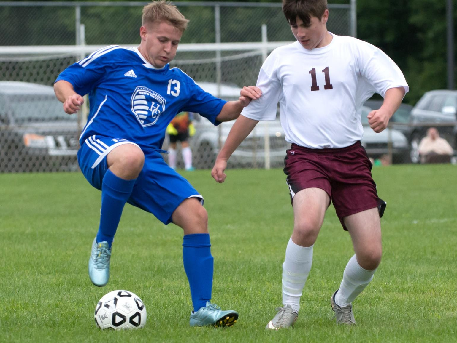 Harper Creek's Josh Fleisher (13) works to keep the ball in play and away from Delton Kellog's Patrick Grubius.