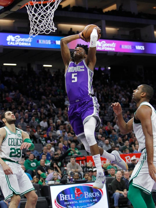 Sacramento Kings guard De'Aaron Fox (5) breaks away for a dunk against the Boston Celtics during the first half of an NBA basketball game in Sacramento, Calif., Sunday, March 25, 2018. (AP Photo/Steve Yeater)