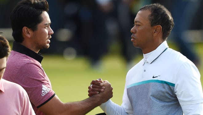 Jul 18, 2015; St. Andrews, Fife, SCT; Tiger Woods shakes hands with Jason Day on the 18th green after the finishing his second round on the third day of the 144th Open Championship at St. Andrews - Old Course. Mandatory Credit: Ian Rutherford-USA TODAY Sports