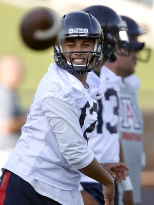 Quarterback Anu Solomon heaves a throw to a target receiver near the sidelines while running offensive drills on the opening day of practice for the University of Arizona football team on Aug. 5, 2015.