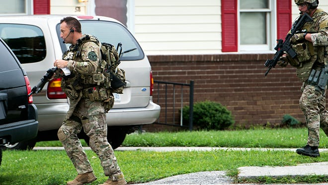 Law enforcement officers move toward the house where James Brown Jr., 49, was involved in a standoff with police, which lasted approximately three hours Monday.