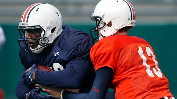 Auburn quarterback Sean White (13) hands off to running back Kamryn Pettway during practice in New Orleans, Thursday, Dec. 29, 2016, for the Sugar Bowl NCAA college football game, which will be played Jan. 2, 2017 against Oklahoma.
