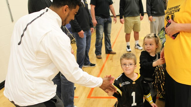This week's Kid Captain, Lincoln Ortman of North Liberty, high-five's Iowa running back Jordan Canzeri during a pep rally for Ortman at North Bend Elementary on Thursday, Nov. 5, 2015.