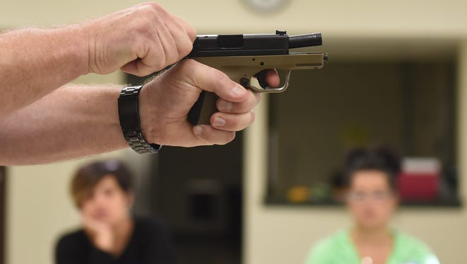Gary Smith, owner of Point Blank Defense, shows the proper technique for racking the slide of a handgun during a training course offered at the York Township park building on Saturday, Oct. 15, 2016.