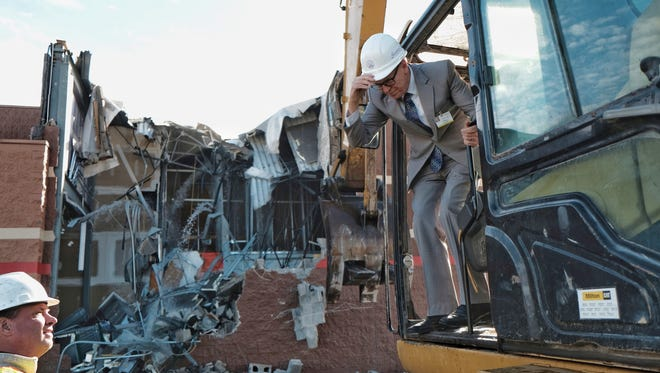 Southfield Mayor Kenson Siver gets off an excavator after helping tear down a section of a former Target location at the site of the Northland Mall in Southfield on Thurs., October 26, 2017.