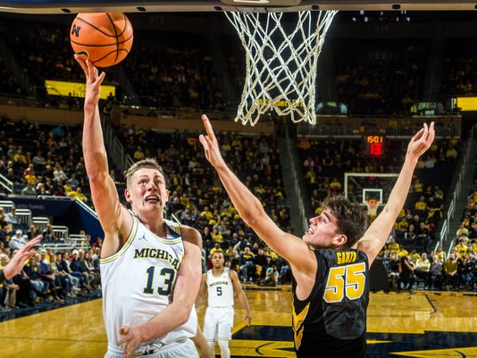 Michigan forward Moritz Wagner (13) attempts a basket, defended by Iowa forward Luka Garza (55) in the first half of an NCAA college basketball game at Crisler Center in Ann Arbor, Mich., Wednesday, Feb. 14, 2018. (AP Photo/Tony Ding)