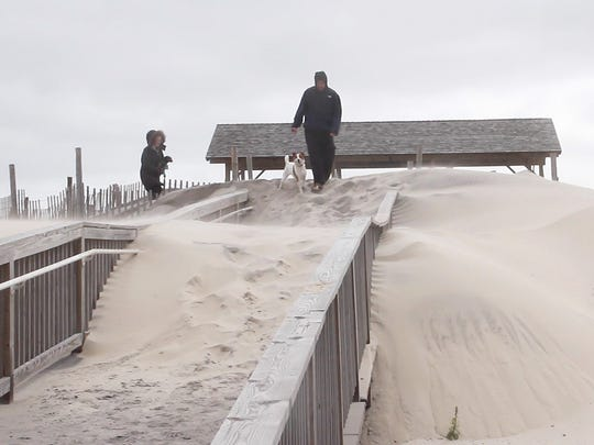 Sarah Gibson and Matt Pupino of Beach Haven had to scale a sand dune on the walkway to the fifth St. Pavillion in order to get to the beach to walk their dogs. There is substantial lose of sand on the beach from this latest nor'easter.