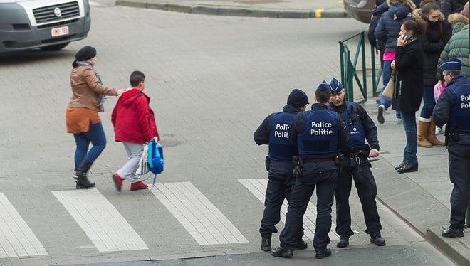 People cross the road as police secure the area in Brussels Tuesday March 15, 2016, after police launched an anti-terror raid linked to last year's Paris attacks in a Brussels neighborhood and three police officers were slightly injured when shots were fired, officials said. A police official, who requested anonymity because the operation was still ongoing, said the exact circumstances of the incident were still unclear, or whether the police officers were struck by bullets or injured in another way.