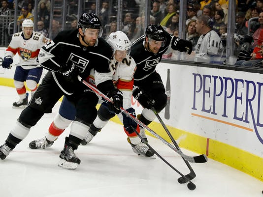 Florida Panthers center Connor Brickley, center, battles for the puck with Los Angeles Kings defenseman Alec Martinez, left, and defenseman Kurtis MacDermid during the first period of an NHL hockey game in Los Angeles, Saturday, Nov. 18, 2017. (AP Photo/Chris Carlson)