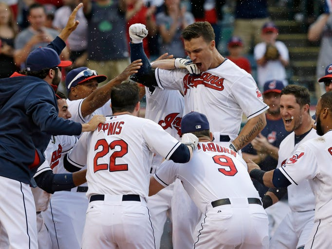Cleveland Indians' Zack Walters, top, is mobbed by teammates after Walters hit a game-winning solo home run off Arizona Diamondbacks relief pitcher Randall Delgado in the ninth inning of the first baseball game of a doubleheader, Wednesday, Aug. 13, 2014, in Cleveland. The Indians defeated the Diamondbacks 3-2.