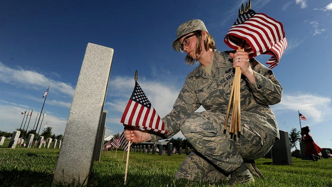 Airman 1st Class Esther Spaulding places flags on graves on Friday, May 26, 2017, at the Texas State Veterans Cemetery at Abilene.