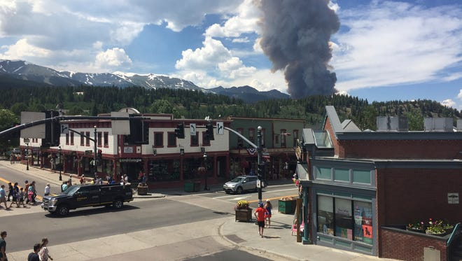 FILE - This Wednesday, July 5, 2017 file photo provided by Tony Cooper a wildfire burning near Breckenridge, Colo. The fire has not spread much since this dramatic flareup. Residents in the mountain town are under orders to be ready to leave if that changes but, in the meantime, it continues to welcome visitors that help drive its economy. (Tony Cooper via AP, File)
