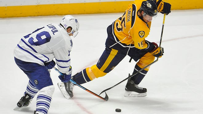 Predators center Craig Smith (15) breaks his stick with the help of Maple Leafs right wing Joffrey Lupul (19) on Thursday.