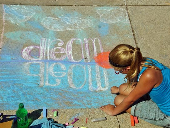 A child works on her chalk art  creation during last