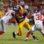 Washington tight end Logan Paulsen is tackled by Giants linebacker Jameel McClain (53) and cornerback Trumaine McBride (38) in the second quarter on Sept. 25. The Giants won 45-14.