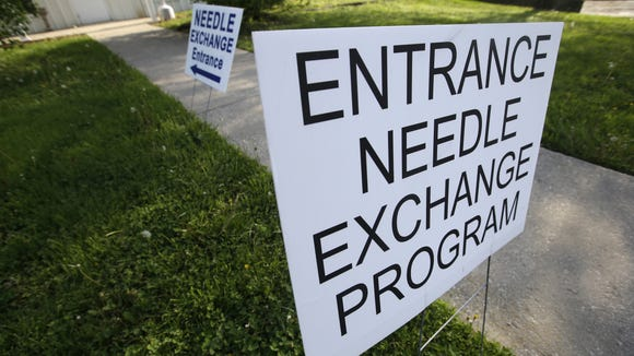 Signs show the entrance to the needle exchange program at the Austin Community Outreach in Austin, Ind. Indiana health officials trying to contain an HIV outbreak tied to needle-sharing among drug users are getting helping from specialists from other states in tracking down about 130 additional people who also may be infected.