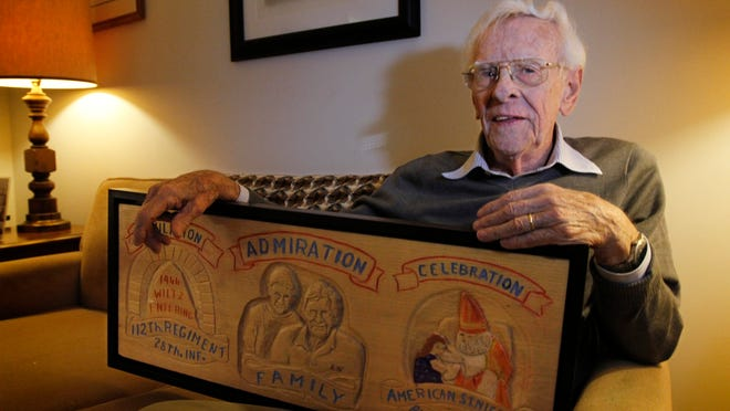 World War II Army veteran Richard Brookins, seen here in his Pittsford home, holds one of the many gifts he's received over the years depicting him as St. Nicolas. Brookins first dressed up as St. Nicolas in 1944 for a party held for children in Wiltz, Luxembourg. This hand-carved wooden plaque was created by a man in Toronto, Canada.