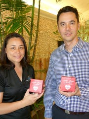 B&G Pacific CEO Marie Guerrero, left, and Guam Visitors Bureau President and CEO Nathan Denight with boxes of the Visit Guam 2017: Year of Love edition of Latte Stone Cookies.