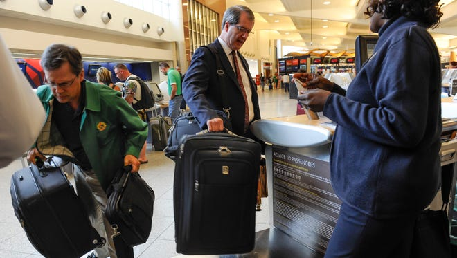Passengers check luggage at Hartsfield-Jackson Atlanta International Airport. Many airlines charge for checked bags.