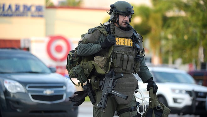 An Orange County Sheriff's Department SWAT member arrives at the scene of a fatal shooting at Pulse Orlando nightclub in Orlando, Fla.