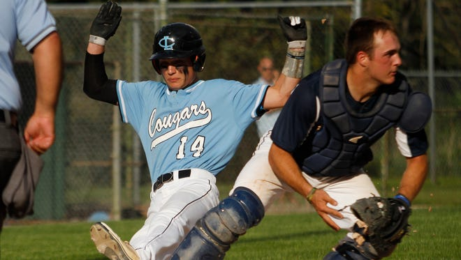 Lansing Catholic's Rob Ruiter slides into home but is called out against DeWitt catcher Connor Grice May 18, 2015 during the Diamond Classic.