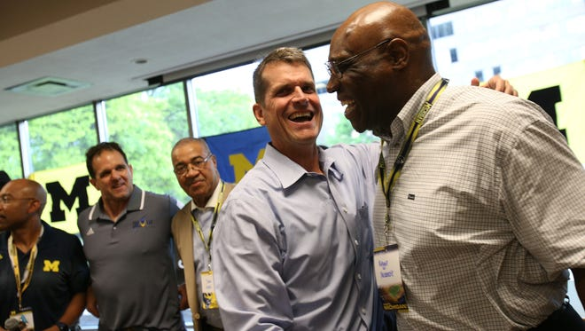 Michigan coach Jim Harbaugh, left, shakes hands with Reggie McKenzie, a former U-M guard, during the Michigan Football Clinic at the Horatio Williams Foundation building in Detroit on Wednesday, May 27, 2015.