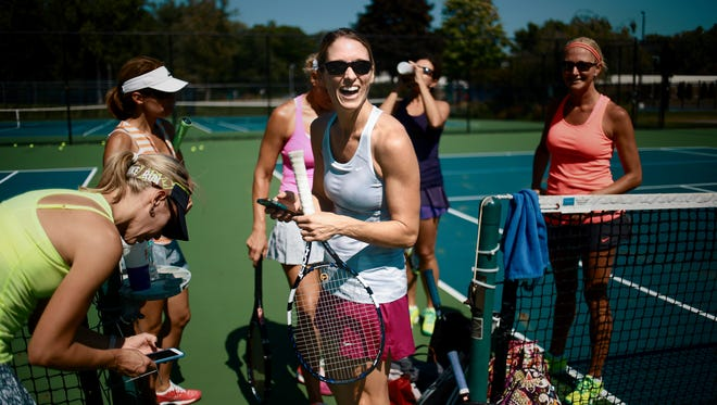 Marni Young is surrounded by other women practicing tennis at Beachwood tennis and swim club in Troy.