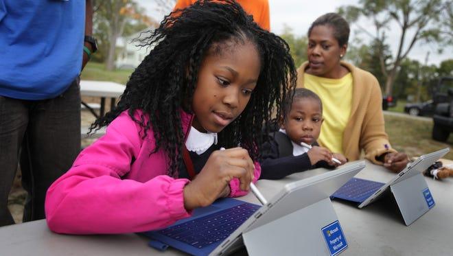 Orissa Calhoun Bey and her brother Iggi Calhoun Bey explore games on a tablet as their mother, Stacy Calhoun Bey, looks on.